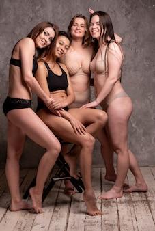 Piękne kobiety z nadwagą i szczupłe w beżowo-czarnym kostiumie kąpielowym na szarym tle. ciało pozytywne. większy rozmiar