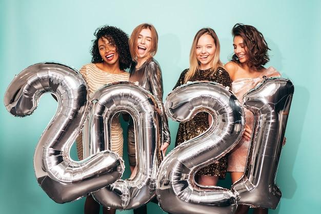 Piękne kobiety z okazji nowego roku. szczęśliwa wspaniała kobieta w stylowe seksowne sukienki imprezowe trzymając srebrne balony 2021, zabawę na imprezie sylwestrowej. uroczystość świąteczna