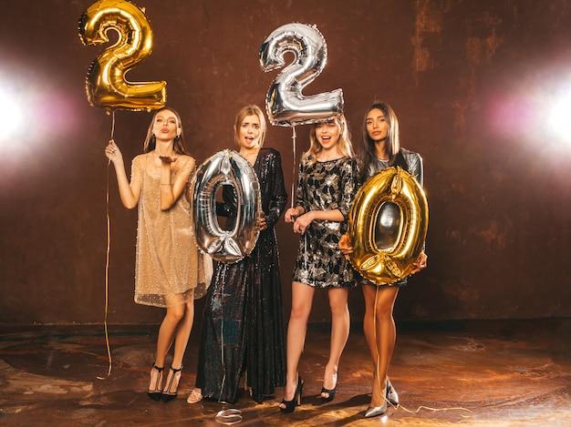 Piękne kobiety z okazji nowego roku. szczęśliwe, przepiękne dziewczyny w stylowych seksownych sukienkach na imprezach ze złotymi i srebrnymi balonami 2020, bawiące się na imprezie sylwestrowej. święto bożego narodzenia. wspaniałe modele