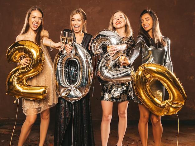 Piękne kobiety z okazji nowego roku. szczęśliwe wspaniałe dziewczyny w stylowych seksownych sukienek