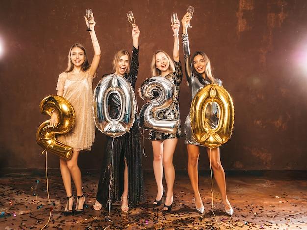 Piękne kobiety z okazji nowego roku. szczęśliwe, wspaniałe dziewczyny w stylowych seksownych sukienkach, trzymając złote i srebrne balony 2020, bawiące się na imprezie sylwestrowej. noszenie i podnoszenie flet szampana