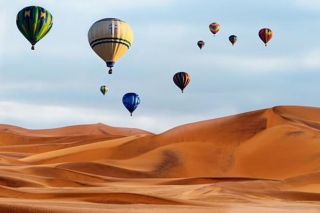 Piękne kolorowe balony na ogrzane powietrze i dramatyczne chmury nad wydmami na pustyni namib