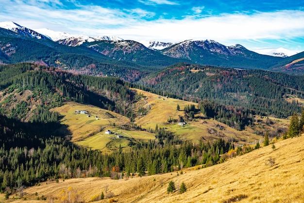 Piękne kolorowe lasy porastające karpaty i mała wioska na tle ciepłego jesiennego nieba