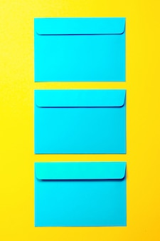 Piękne kolorowe niebieski envelops na żółtym tle, moda s