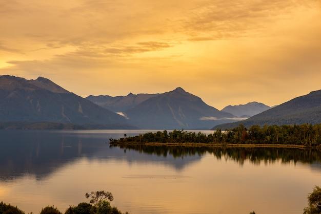 Piękne krajobrazy jeziora te anau i odbicia wody pod żywym pomarańczowym niebem o zachodzie słońca