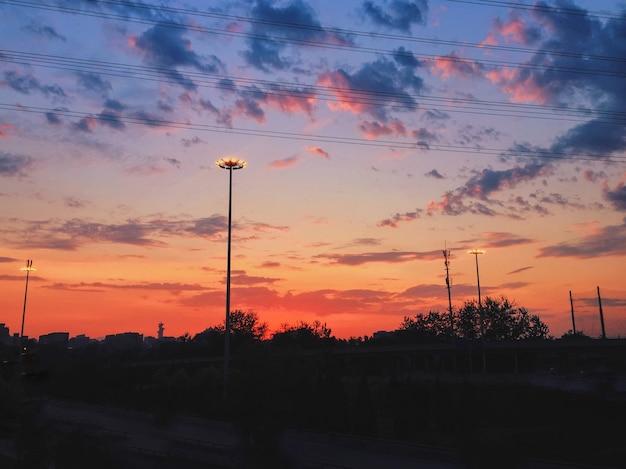 Piękne krajobrazy nieba słońca z kolorowymi chmurami nad pejzażem miejskim