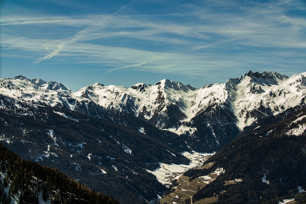 Piękne krajobrazy pasma gór skalistych pokrytych śniegiem pod zachmurzonym niebem