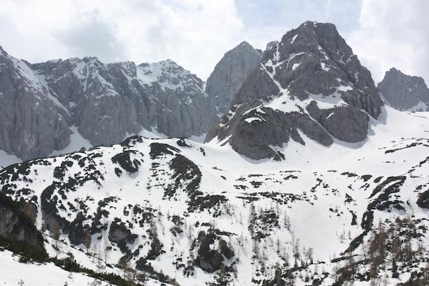 Piękne krajobrazy pasma wysokich skalistych gór pokrytych śniegiem