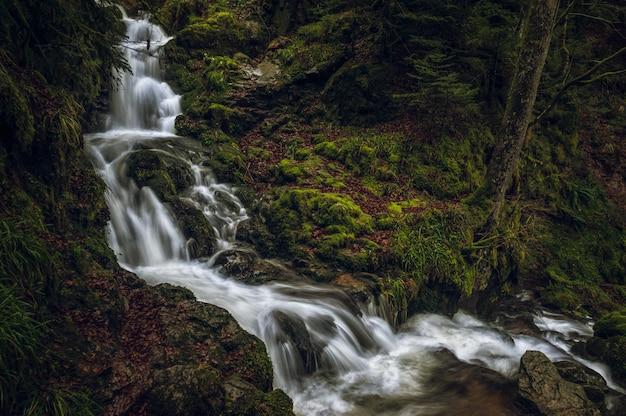 Piękne krajobrazy potężnego wodospadu w lesie w pobliżu omszałych formacji skalnych
