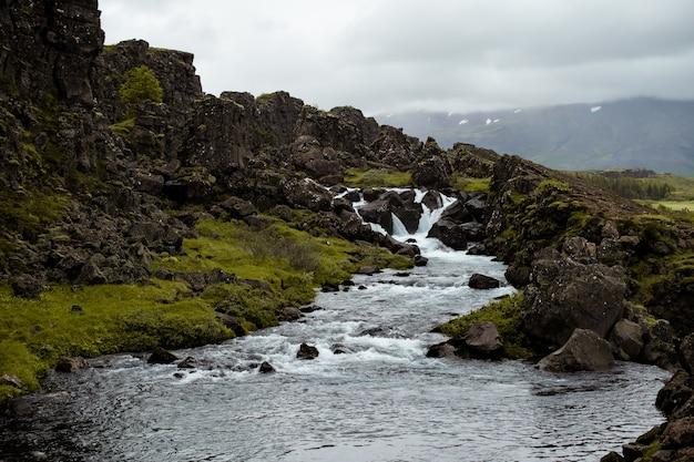 Piękne krajobrazy rzeki płynącej w pobliżu formacji skalnych na islandii