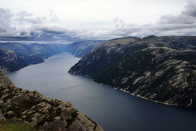 Piękne krajobrazy słynnych klifów preikestolen w pobliżu jeziora pod zachmurzonym niebem w stavanger w norwegii