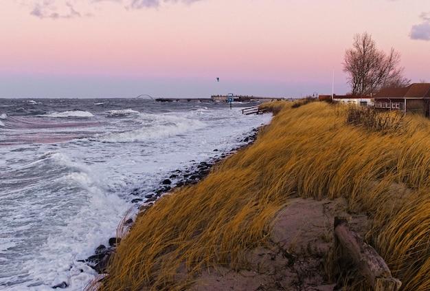Piękne krajobrazy trawiastego wzgórza nad morzem podczas zachodu słońca