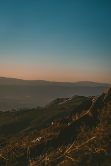 Piękne krajobrazy zachodu słońca nad zielonym krajobrazem z górami skalistymi