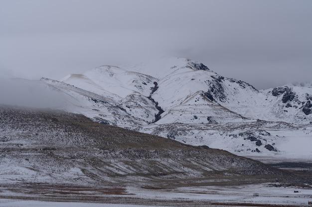 Piękne krajobrazy zaśnieżonych gór w ciemny, ponury dzień