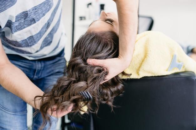 Piękne kręcone fryzury młodej brunetki w salonie fryzjerskim