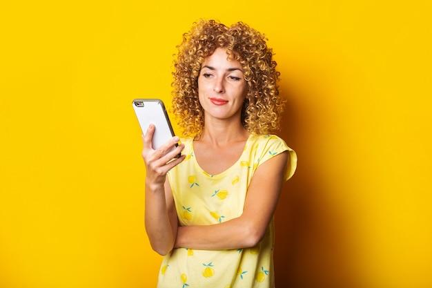 Piękne kręcone młoda kobieta uśmiechając się trzyma telefon na żółtym tle.