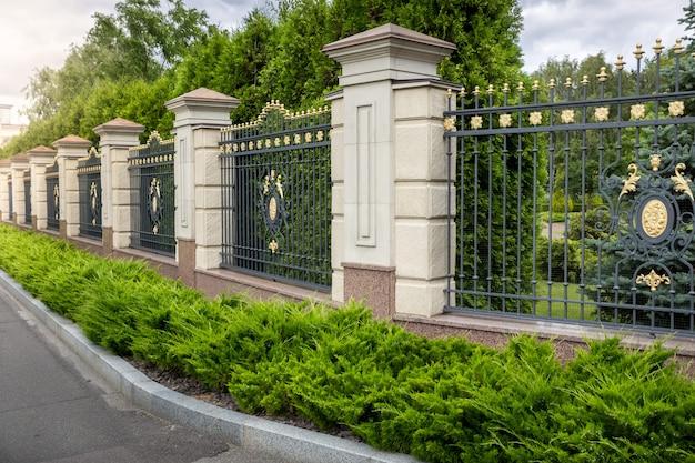 Piękne kute ogrodzenie pomalowane złotem przy wejściu do luksusowej willi