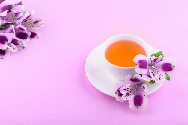 Piękne kwiaty astromerii. herbata ziołowa w białej filiżance i białym spodku