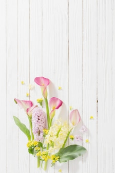 Piękne kwiaty na białym drewnianym tle