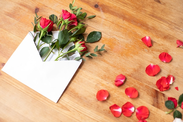 Piękne kwiaty na drewnianym stole z kopertą. praca kwiaciarni. dostawa kwiatów.