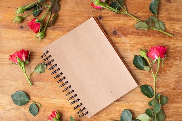 Piękne kwiaty na drewnianym stole z notatnikiem. praca kwiaciarni. dostawa kwiatów.