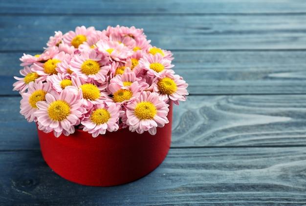 Piękne kwiaty w pudełku prezentowym na drewnianym tle