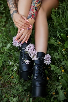 Piękne kwiaty w rękach dziewczyny z tatuażami, kosmetyki. letnie kwiaty i jasny makijaż na paznokciach dłoni kobiety. manicure i różowe paznokcie