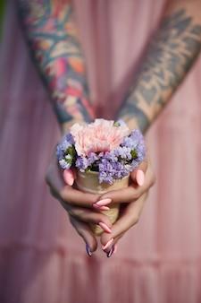 Piękne kwiaty w rękach dziewczyny z tatuażami