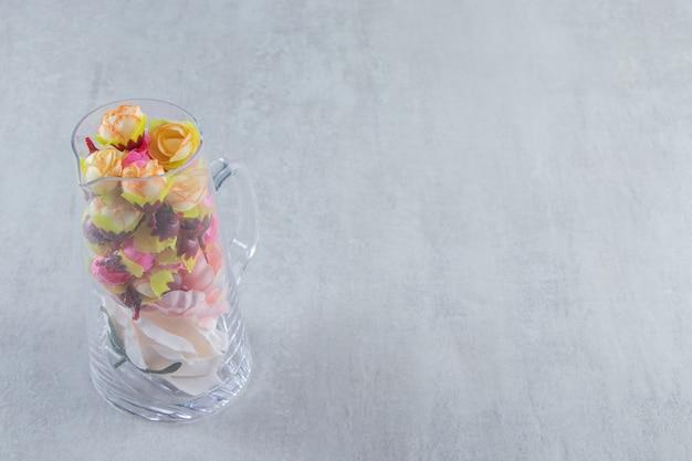 Piękne kwiaty w szklanej karafce, na białym stole.