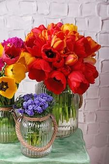 Piękne kwiaty w wazonach na tle ściany