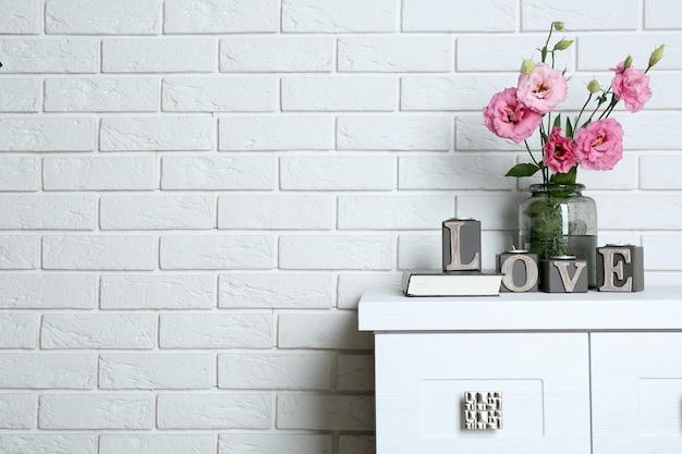 Piękne kwiaty w wazonie ze słowem miłość na powierzchni ściany z cegły