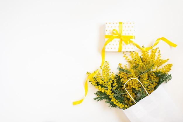Piękne kwiaty z opakowaniem i obecną kompozycją. gałęzie kwiaty mimozy na białym tle. walentynki, wielkanoc, urodziny, dzień matki. płaski płaski, widok z góry, kopia przestrzeń. wiosenna wyprzedaż