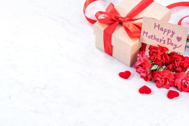 Piękne kwitnące goździki z czerwoną wstążką łuk pudełko na białym tle na nowoczesnym marmurowym biurku, z bliska, kopia przestrzeń