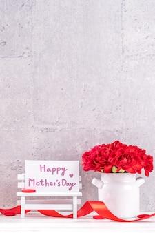 Piękne kwitnące goździki z pudełkiem z czerwoną wstążką na białym tle na jasnym tle szarym biurku, z bliska, kopia przestrzeń