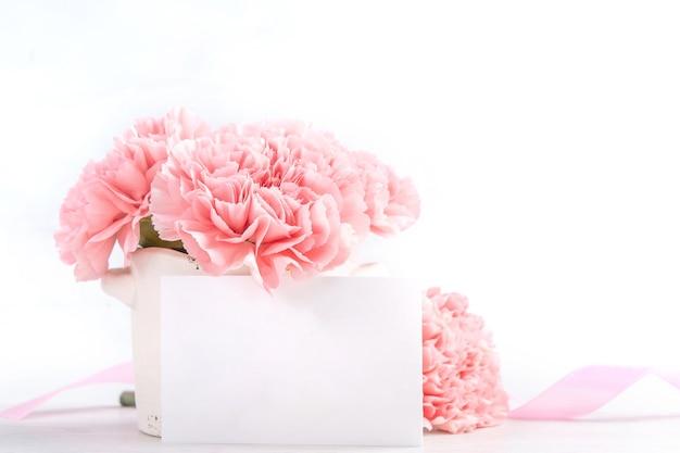 Piękne kwitnące różowe goździki delikatne dziecko w białym wazonie na białym tle na jasnym tle, z bliska, kopia przestrzeń
