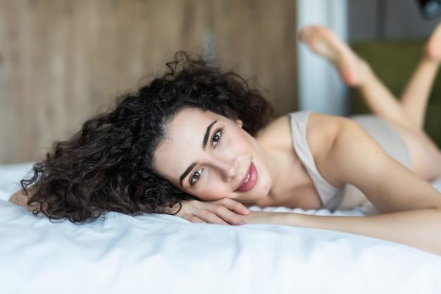 Piękne ładne kobiety w bieliźnie, leżąc na białej poduszce