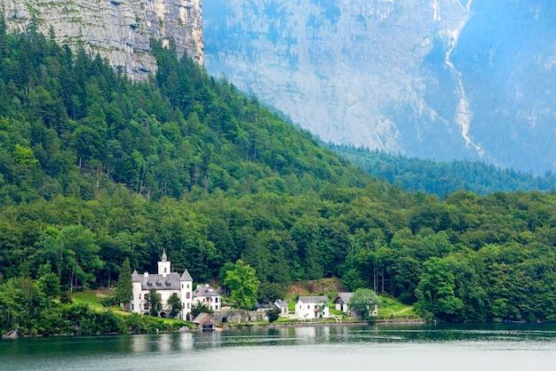 Piękne letnie alpejskie jezioro hallstatter see, widok na austrię i zamek daleko.