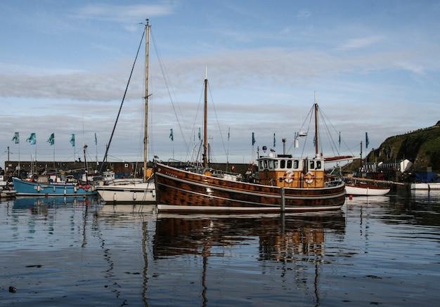 Piękne łodzie na molo z zachmurzonym niebem