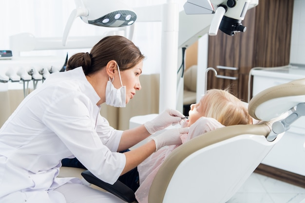 Piękne małe dziecko na przeglądzie dentystycznym w nowoczesnej klinice.