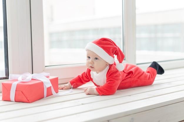 Piękne małe dziecko obchodzi boże narodzenie. święta nowego roku. dziecko w świątecznym stroju iw