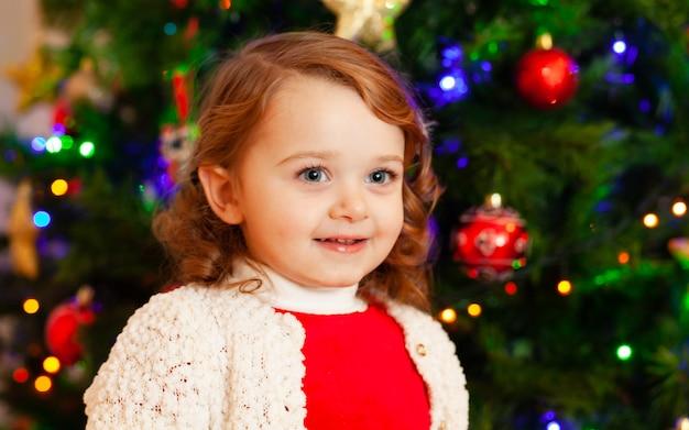 Piękne małe dziecko w pobliżu choinki.