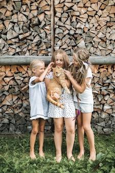 Piękne małe trzy dziewczynki w przypadkowych ubraniach bawiące się z czerwonym kotem, patrząc na siebie