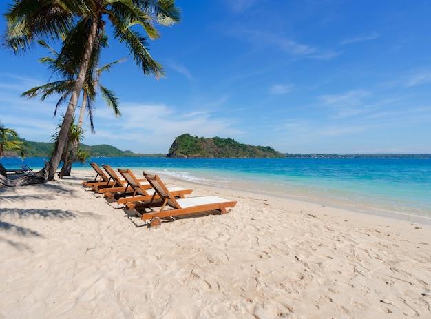 Piękne malownicze krzesła na białej, piaszczystej plaży w pobliżu drzew kokosowych z błękitnym morzem i niebem na wyspie w lecie, relaks na plaży na wyspie rayang, rayong, tajlandia