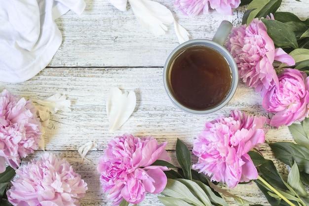 Piękne martwa natura z filiżanką herbaty i piwonie. widok z góry