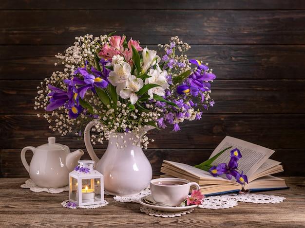 Piękne martwa natura z kwiatami, świecą, książką i filiżanką