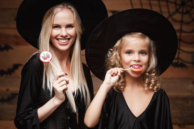 Piękne matka caucasian i jej córka w strojach czarowniczy świętuje halloween z halloween krystalicznego