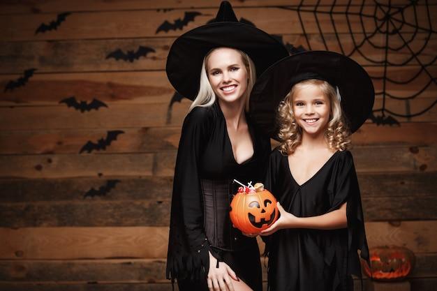 Piękne matka caucasian i jej córka w stroje czarownice świętuje halloween z udostępniania cukierków halloween
