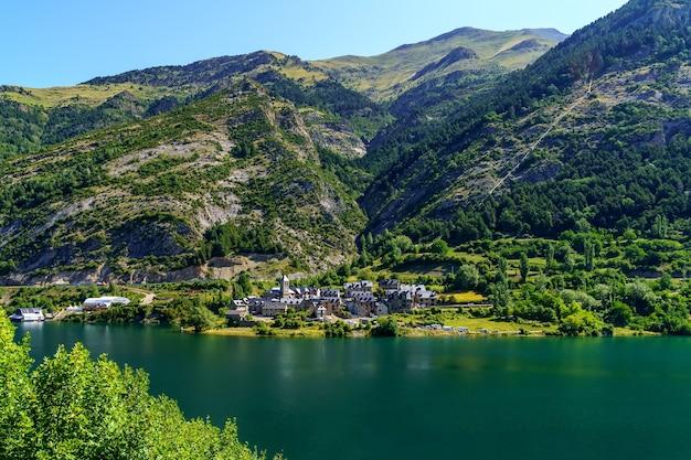 Piękne miasto nad brzegiem dużego jeziora między wysokimi górami w pirenejach, huesca, aragon, hiszpania. europa.