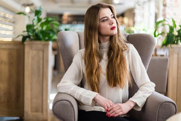 Piękne młoda dziewczyna z profesjonalnych makijażu i fryzura siedzi w restauracji.