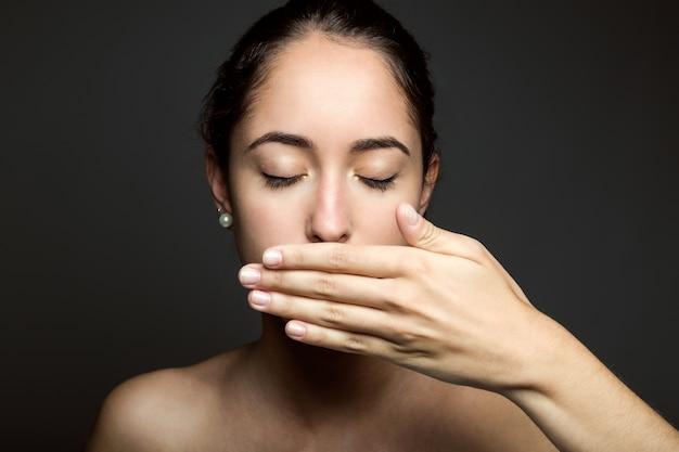 Piękne młoda kobieta obejmujące jej ustach ręką. odosobniony.